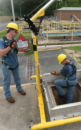 two workers use fall protection PPE to climb into a hole