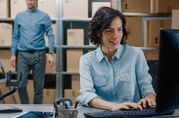 Female Inventory Manager Sitting at Her Desk and Using Personal Computer, Worker Puts Packages on the Designated Shelf. In the Background Rows of Cardboard Boxes with Products Ready For Shipment.